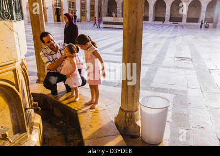 Syrian father washing his baby daughters at the ablutions fountain of the Great Mosque of Aleppo. Syria - Stock Photo