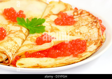 Pancakes with red caviar on a plate on white background - Stock Photo