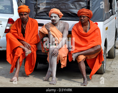 A group of Sadhus, Hindu holy men, rest near holy Ganges river during Kumbh festival. - Stock Photo