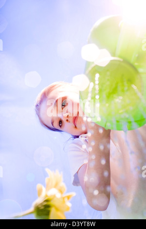 Young girl/child pouring water from green watering can onto flower on sunny day - Stock Photo