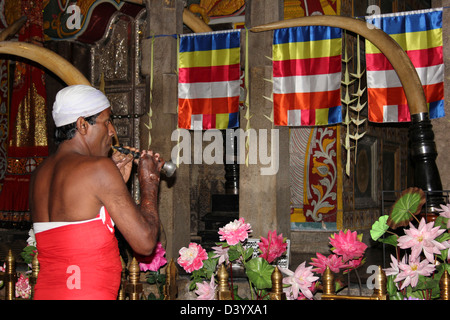Temple Guardian Blowing Horanewa Horn At The Temple of the Sacred Tooth Relic, Kandy - Stock Photo
