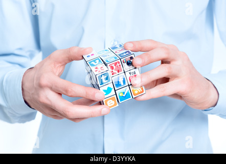 Businessman solving rubik's cube with logotypes of well-known social media brand's. - Stock Photo