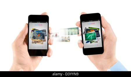 Two hands holding mobile smartphones while transferring pictures from one to another. - Stock Photo