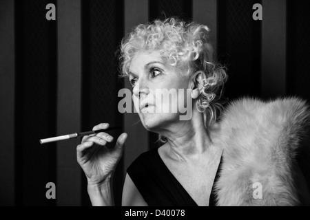 Bond senior woman holding a cigarette holder - Stock Photo