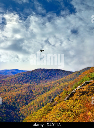 Long distance view of mountains in the fall with a small airplane flying over. - Stock Photo