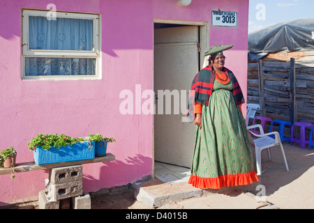 Herero woman in traditional colourful dress in front of her house in township near Swakopmund, Namibia, South Africa - Stock Photo