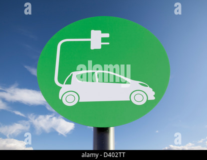 Green sign indicating a charging point for electric vehicles, sunny blue sky added in post-production - Stock Photo