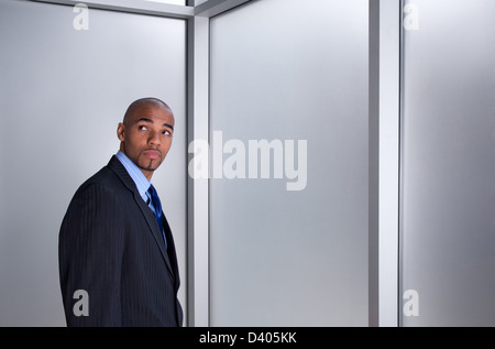 Young businessman looking anxious and worried, standing beside a window. - Stock Photo