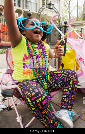 Young girl shouting for beads on Mardi Gras day, New Orleans. - Stock Photo