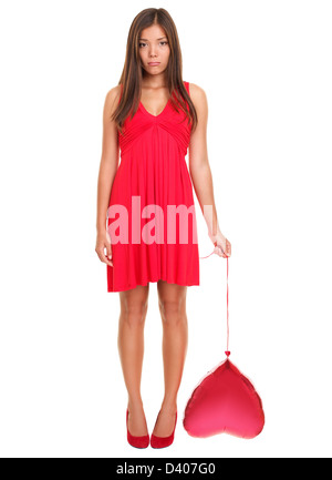 Portrait of sad Asian / Caucasian young woman in love holding red heart balloon standing isolated on white background - Stock Photo