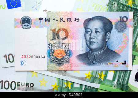 10 Yuan banknote with Mao Zedong and 100 Euro banknotes as background - Stock Photo