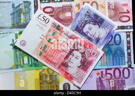 20 and 50 Pounds banknotes with portrait of Queen Elizabeth II and Euro banknotes in background - Stock Photo