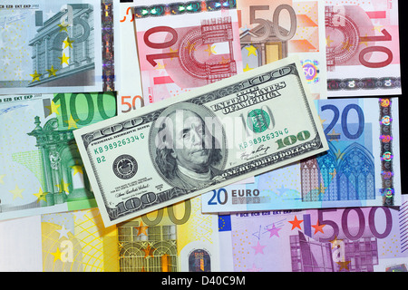 100 Dollars banknote with Benjamin Franklin, USA (2006) and Euro banknotes of different denominations as background - Stock Photo