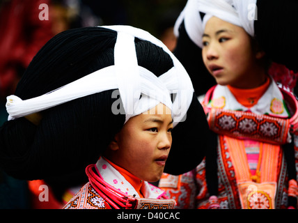 A Long Horn Miao little girl in traditional costumes dancing to celebrate the Tiao Hua festival / spring festival - Stock Photo
