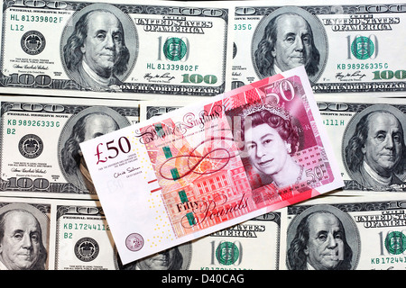 20 and 50 Pounds banknotes with portrait of Queen Elizabeth II and 100 Dollars banknotes in background - Stock Photo