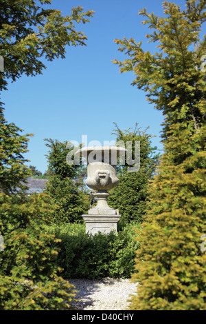a classic garden urn in a small formal garden - Stock Photo
