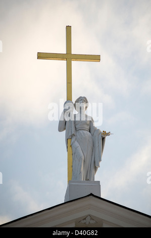 The cathedral in Katedros square, Vilnius, showing a statue holding a golden cross - Stock Photo