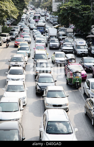 It's a photo of the traffic jam in Bangkok in Thailand during the Rush hours. The road is full of cars, trucks and - Stock Photo