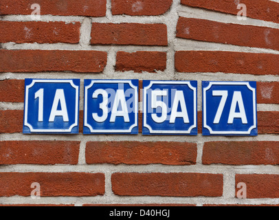 Multiple house numbers on wall - Stock Photo