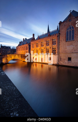 Beautiful old houses and a bridge reflected in the charismatic canals from Bruges (Brugge) - Belgium. - Stock Photo