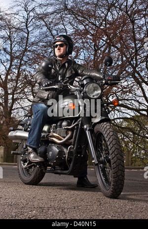Man in black leathers on Triumph scrambler motorbike, London - Stock Photo