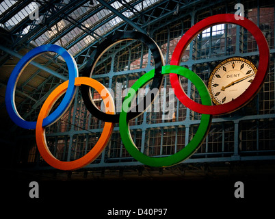 Olympic rings hanging at St Pancras station showing clock at 20:12 pm - Stock Photo