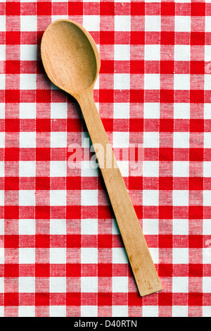 the wooden spoon on checkered tablecloth - Stock Photo