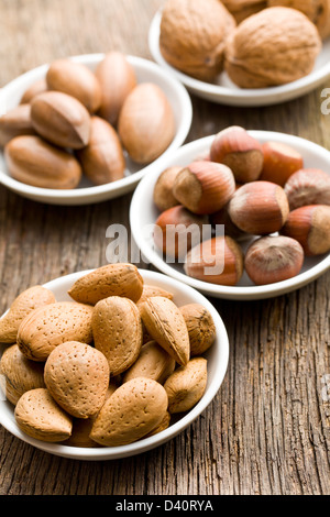various nuts in ceramic bowls on woden table - Stock Photo