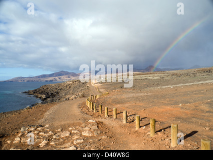 footpath between puerto del carmen and puerto calero with fermes mountains in the distance lanzarote canary islands - Stock Photo