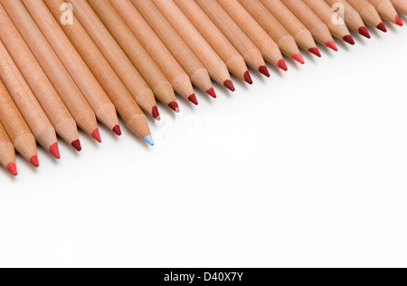 Line of red colouring pencils with one blue pencil sticking out - difference concept - Stock Photo