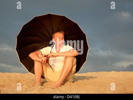 Relaxing man with umbrella on the beach Sardinia Italy - Stock Photo