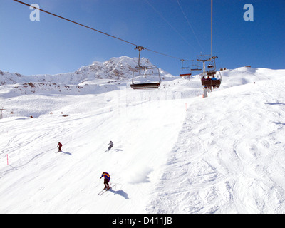 Skiers skiing on the slopes ( piste ), and the Hornli chairlift, Arosa ski resort Switzerland Europe - Stock Photo