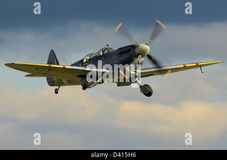Two seat Supermarine Spitfire MkIXT (Mark 9 trainer) takes off with Richard Grace at the controls in a stormy sky. - Stock Photo