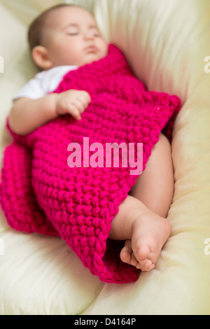 Newborn baby sleeping in bed covered with knitted blanket - Stock Photo