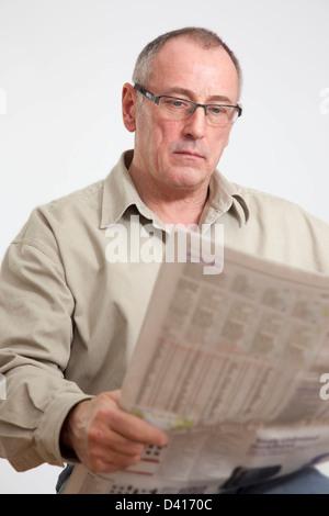 Mature man in 50s, reading a broadsheet newspaper. - Stock Photo