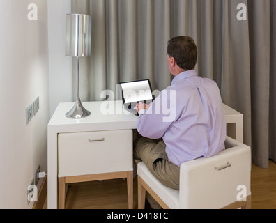 Senior man at modern white table desk and two chairs in hotel room at night - Stock Photo