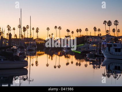 Sunset over residential development by water in Ventura California with modern homes and yachts boats - Stock Photo