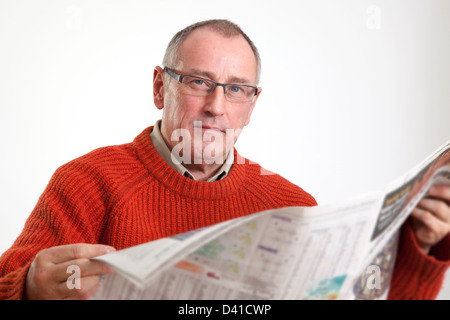 Mature man in 50s wearing sweater, reading a broadsheet newspaper, looking to camera serious. - Stock Photo