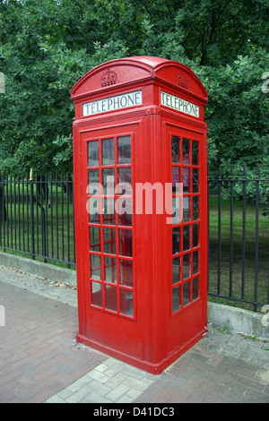 Red telephone box on brick paved street with park, oak trees and iron railings in background - Stock Photo