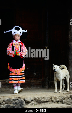 A Long Horn Miao little girl in traditional costume standing with her pet dog by her home. - Stock Photo
