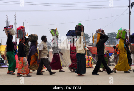 Hindu devotees carry their belongings on their heads as they leave the Kumbh Mela in Allahabad - Stock Photo