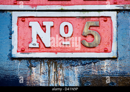 Close-up of a number five sign on the side of an old British Steam engine. - Stock Photo