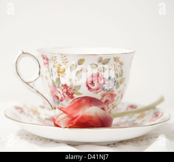 Flowered porcelain tea cup and saucer with tulip on saucer - Stock Photo