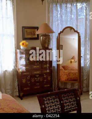 Antique inlaid chest-of-drawers beside cheval glass in front of window with lace curtain in country bedroom - Stock Photo