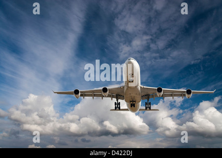 Large commercial airplane flies in blue sky - Stock Photo
