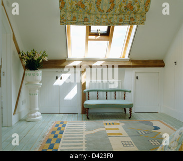 Small blue sofa below Velux window with patterned blind in loft bedroom with pattern rug and plant in pot on china - Stock Photo