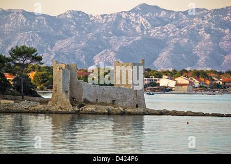 Island of Vir fortress ruins with Velebit mountain in background, Dalmatia, Croatia - Stock Photo