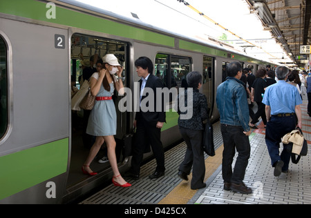 Commuters getting on and off the green Yamanote Loop Line train at the Ueno Station platform in Tokyo. - Stock Photo