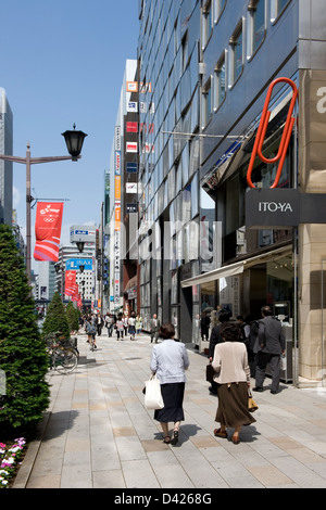 On a sunny afternoon shoppers walking along Chuo-dori (Main Street) in the upscale Ginza shopping district in downtown - Stock Photo