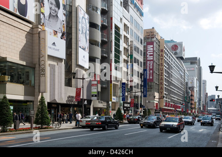 Retail stores and fashion boutiques line both sides of Chuo-dori (Central Street) in upscale Ginza shopping district - Stock Photo